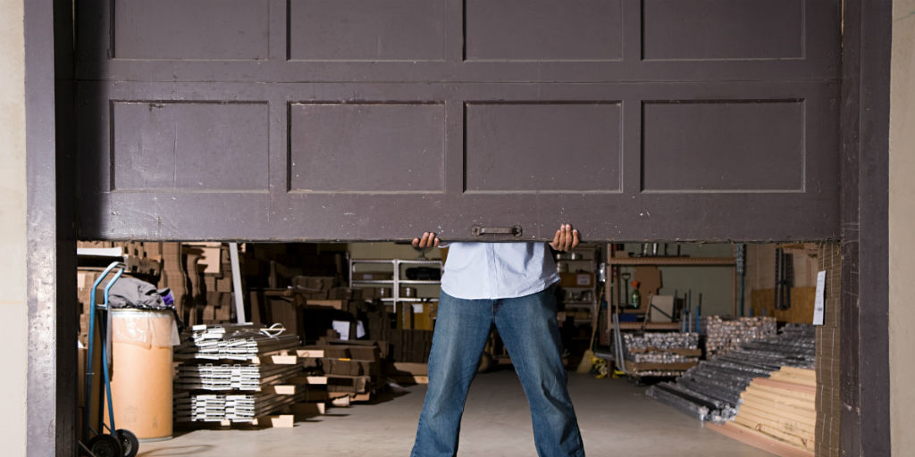 24 hour garage door repair man holding up door